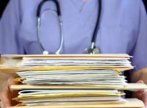 nurse or doctor holding a stack of files in folders